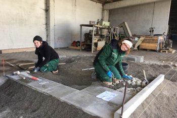 Zwei Mitarbeiterinnen beim Pflastern einer Außenanlage