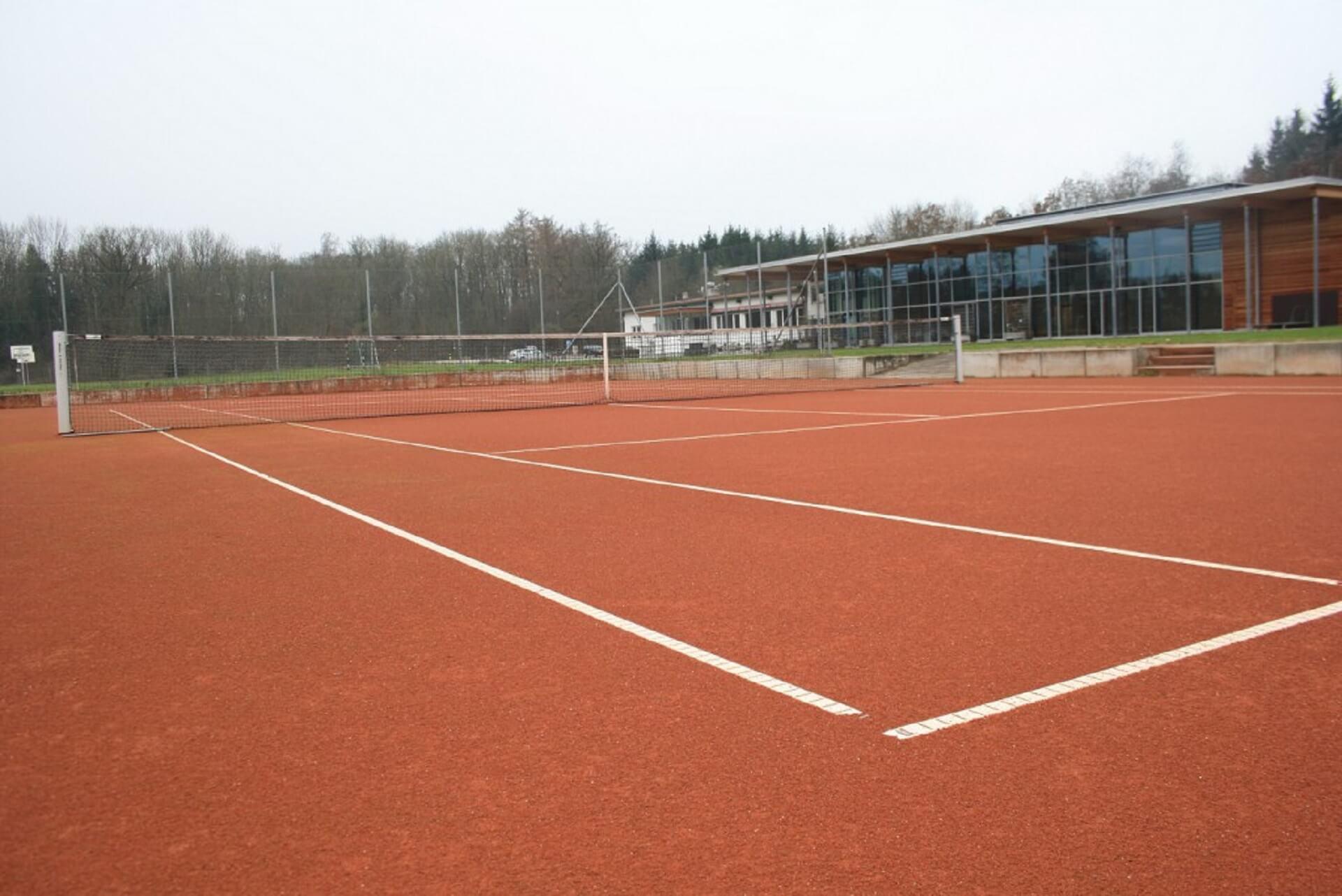Tennisplatz mit anliegender Sporthalle