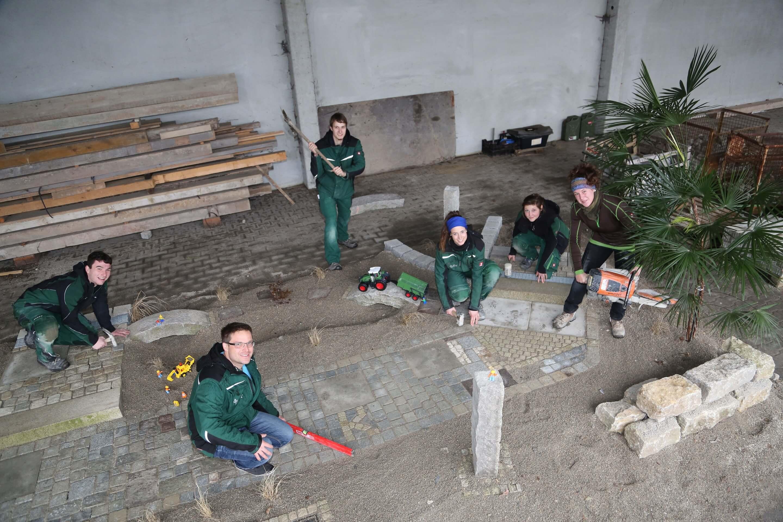 6 Azubis arbeiten an einer Außenanlage