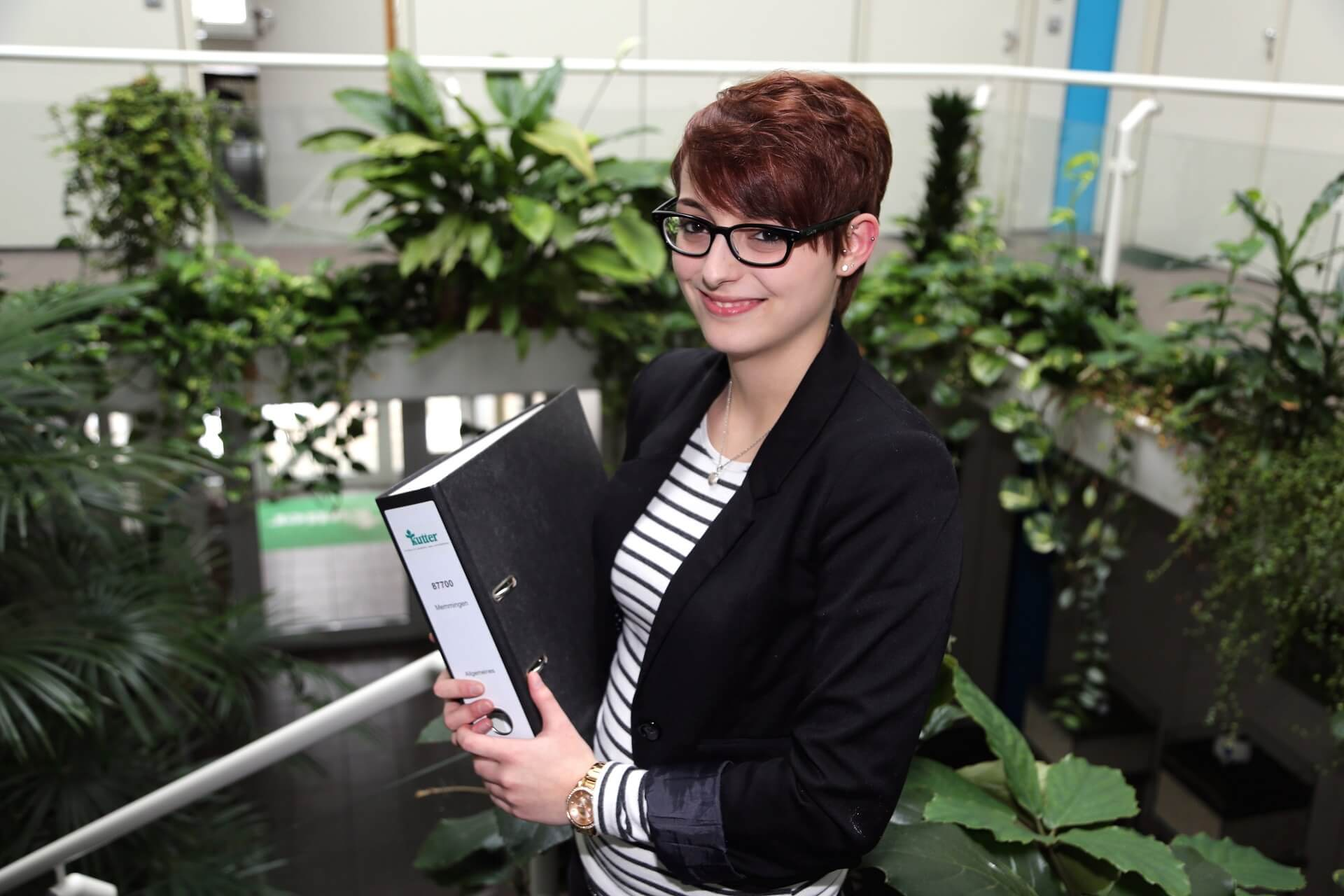 Junge Frau mit kurzen Haaren und Bürokleidung hält einen Ordner und lächelt in die Kamera