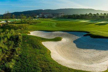 Aufnahme eines Golfplatzes mit Sandbucht unter blauem Himmel