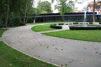 Eine grüne Parkanlage mit einem Stabilizer Weg im Vordergrund