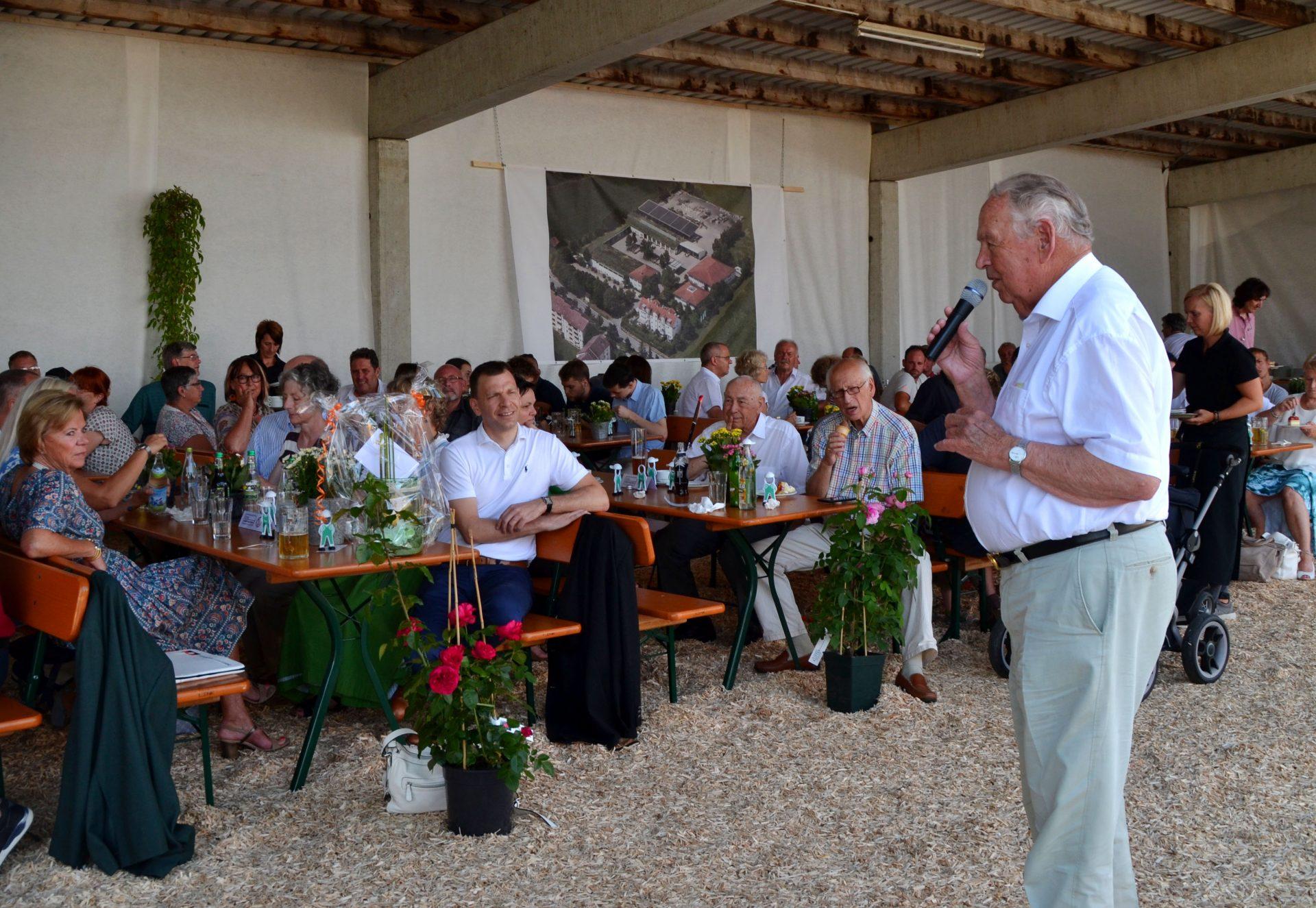 Firmengründer Hermann Kutter (84) schildert beim Sommerfest 2019, wie alles 1959 begann. Sein erster Auftrag: Hecke ausräumen, Rasen mähen, düngen und nachsäen für 55 DM.