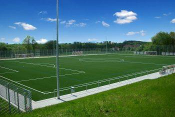 Fußballfeld mir grünem Naturrasen und weißen Markierungen