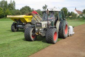 Traktor mit Koro-Fräse trägt Grasnarbe von Rasenspielfeld ab